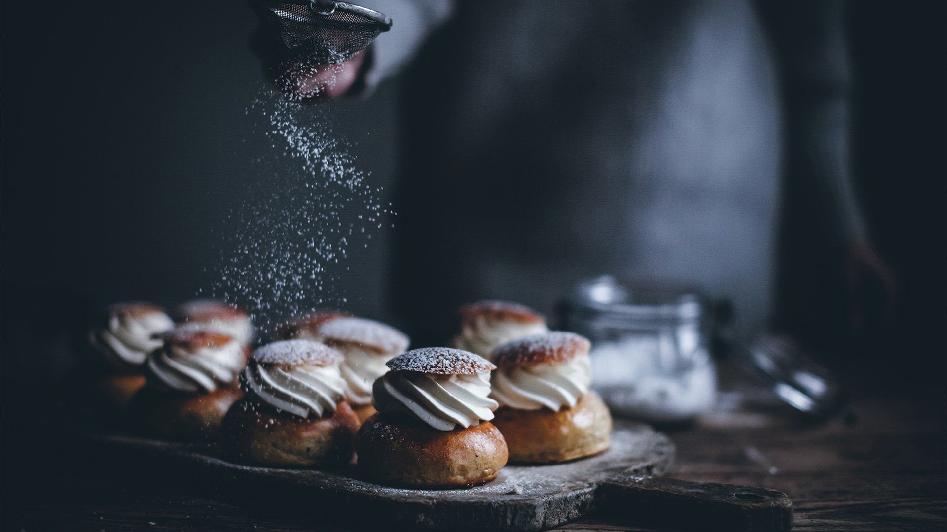 A person dusting icing sugar over pastries filled with piped cream.